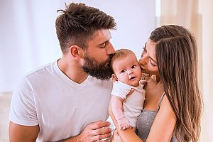 a newborn baby with his newly adopted parents who are both on parental leave for adoption thanks to the help of an employment law attorney
