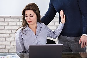 a business woman who is experienced quid pro quo sexual harassment pushing her boss away