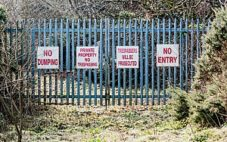 a fence with signs displaying Virginia trespassing laws