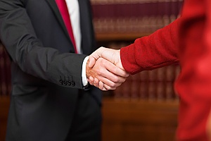 an employment law attorney shaking hands with a client to speak about overtime pay compensation