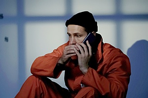 a man in jail making a call to an attorney after being accused of robbery
