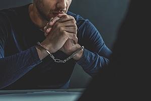 a man in handcuffs being interrogated by an investigator