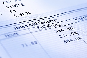 close up view of a paystub showing wages and hours and earnings on it