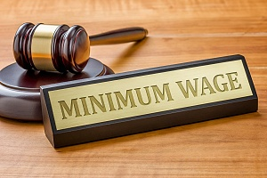 minimum wage placard with a judge gavel on a brown wooden table