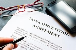 non compete agreement on a table with a pencil and glasses