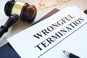wrongful termination on a piece of paper with a judge gavel and a pen on table