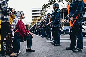 a man kneeling before police officers to protest brutality and excessive force
