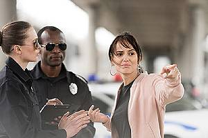 A sad female confronting two police officers. There are different types of police excessive force