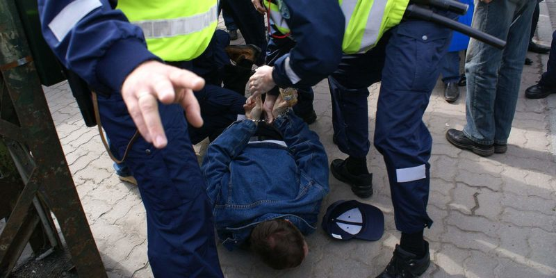 Police officer using excessive force to subdue a protestor