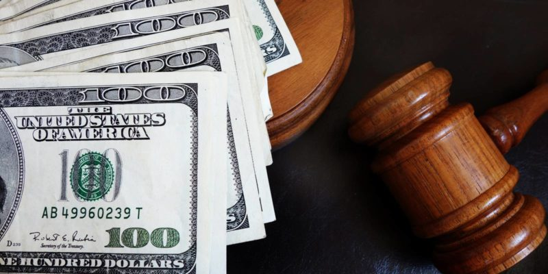 cash settlement of the police brutality case lays next to the gavel