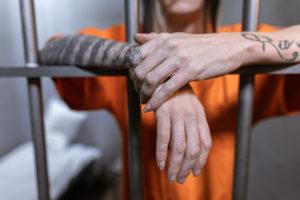 prisoner stands behind cell after unlawful arrest