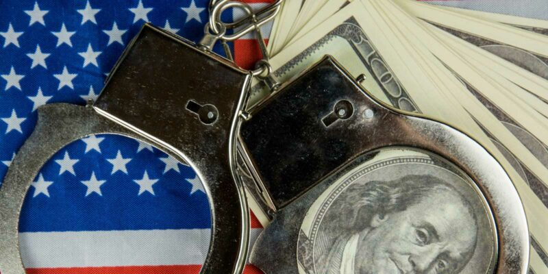 handcuffs used in a false arrest lays on top of the settlement money and flag