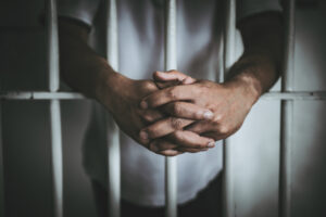 man stand behind bars after being placed under arrest on false charges
