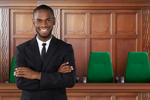 confident attorney In courtroom standing arms crossed
