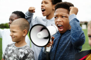 young boy shouting on a megaphone in a protest