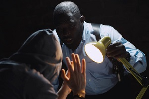 officer interrogating man suspected of crime glowing light of lamp into face