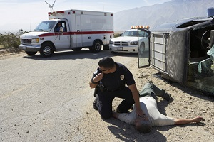 police officer checking pulse of car crash victim