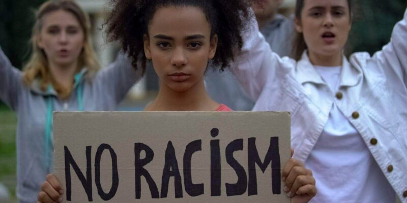 girl holding no racism sign